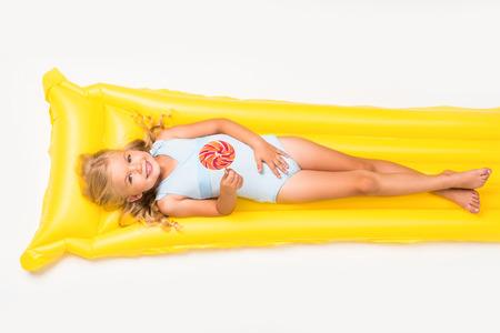 Photo pour adorable smiling little girl holding lollipop and lying on swimming mattress isolated on white  - image libre de droit