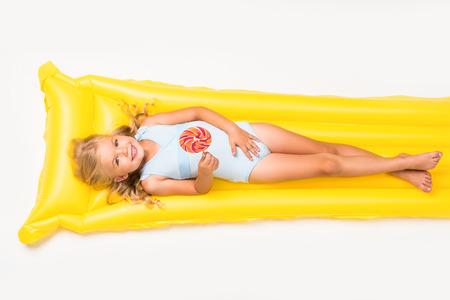 Foto de adorable smiling little girl holding lollipop and lying on swimming mattress isolated on white  - Imagen libre de derechos