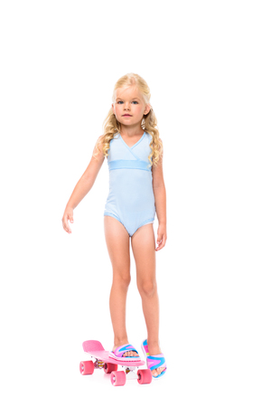 Photo pour adorable little girl in swimsuit standing on skateboard and looking at camera isolated on white - image libre de droit