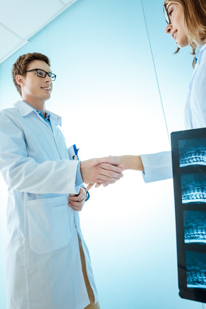 Photo for Young doctors in lab coats shaking hands - Royalty Free Image