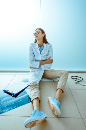 Photo for Young medical interns in a lab coat sitting on a floor in hospital corridor looking exhausted - Royalty Free Image