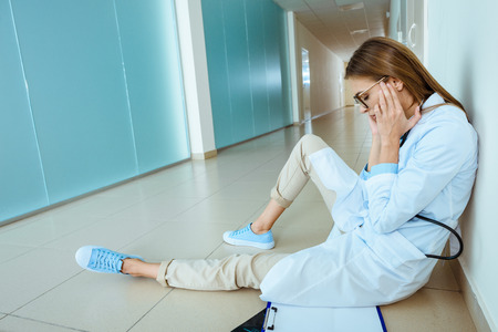 Photo for Young doctor in a lab coat sitting on a floor in hospital corridor and rubbing her temples - Royalty Free Image