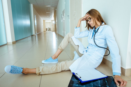 Photo for Young doctor in a lab coat sitting on a floor in hospital corridor touching her head - Royalty Free Image