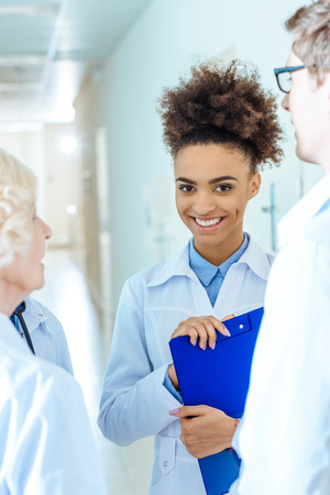 Photo for Young african-american medical intern holding a clipboard and smiling - Royalty Free Image
