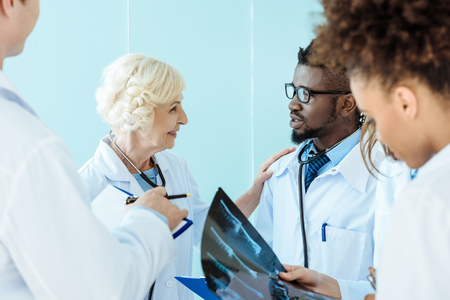 Photo for Senior doctor talking to african-american medical intern and touching him on shoulder - Royalty Free Image