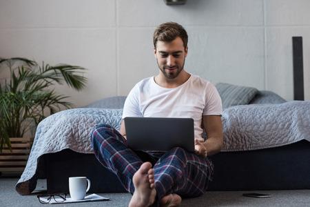 Foto de Young attractive man sitting on floor in his bedroom and working on laptop - Imagen libre de derechos