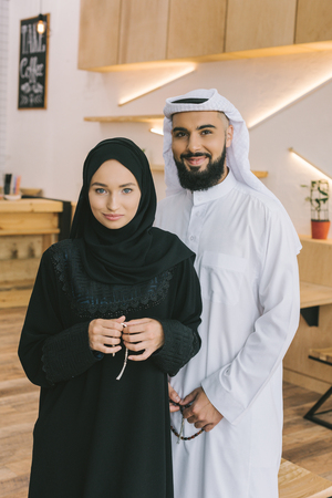 Photo pour muslim couple in traditional clothing standing in modern cafe - image libre de droit