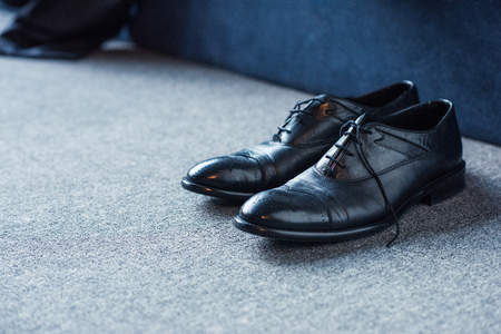 Foto de Black male leather shoes placed on carpet floor - Imagen libre de derechos