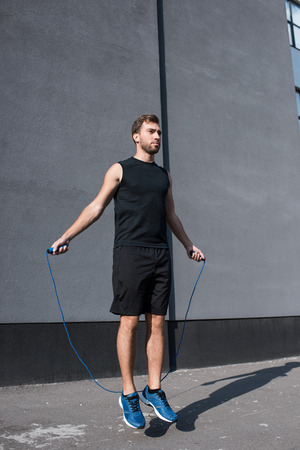 Photo pour Young athletic sportsman in sportswear exercising with a jumping rope outside - image libre de droit