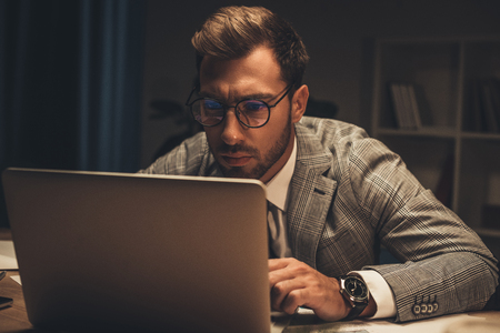 concentrated young businessman working with laptop in dark office