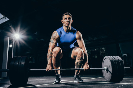 Foto de Young athletic sportsman in sportswear squatting while lifting up a barbell with weights - Imagen libre de derechos