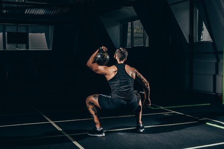 Photo pour Rear view shot of young athletic sportsman squatting and lifting up a kettlebell at gym - image libre de droit