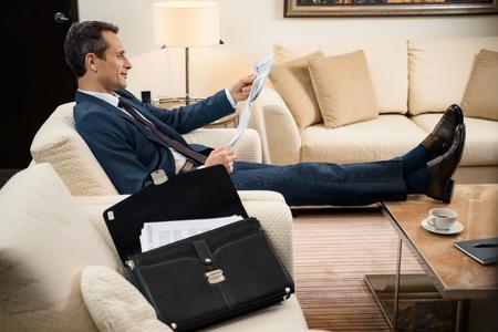 Foto de Businessman in formal suit sitting in armchair and reading a newspaper - Imagen libre de derechos