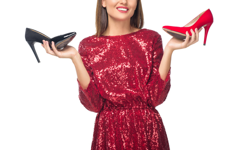 Photo for cropped shot of smiling young woman holding high heeled shoes isolated on white - Royalty Free Image