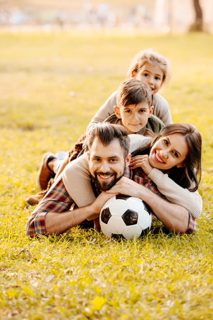 Photo for Happy family with two children lying in a pile on grass in a park - Royalty Free Image