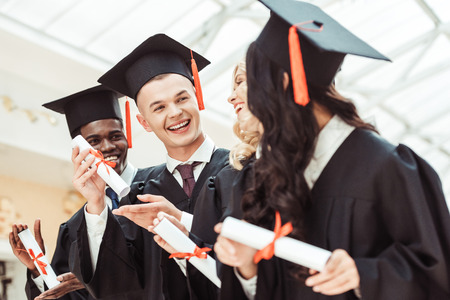 Photo for laughing graduated multiethnic students with diplomas - Royalty Free Image