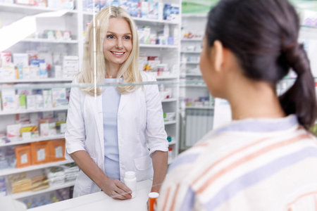 Photo for pharmacist and customer looking at each other in drugstore - Royalty Free Image