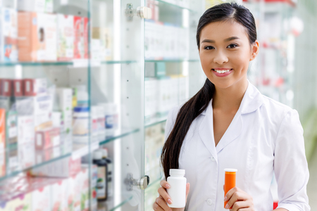 Foto de young pharmacist holding containers with medication and smiling at camera in drugstore - Imagen libre de derechos
