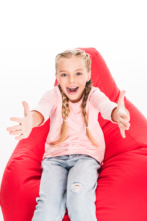 Foto de excited child sitting on a red bean bag with arms outstreched, isolated on white - Imagen libre de derechos