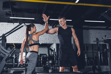 Photo pour sportive couple giving high five to each other in gym - image libre de droit