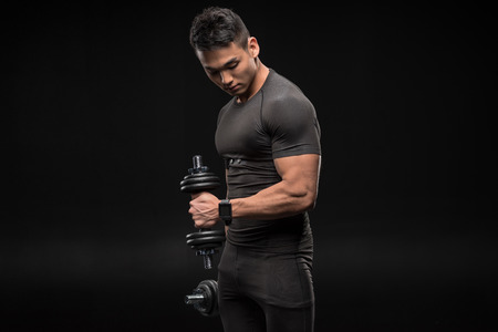 Foto de handsome young asian man in asian man exercising with dumbbells isolated on black - Imagen libre de derechos
