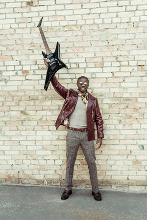 Photo for Young african american man wearing stylish clothes and sunglasses, holding an electrical guitar in outstreched arm - Royalty Free Image