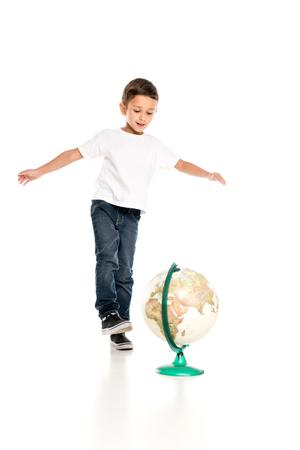 Foto de caucasian little boy standing near globe isolated on white - Imagen libre de derechos