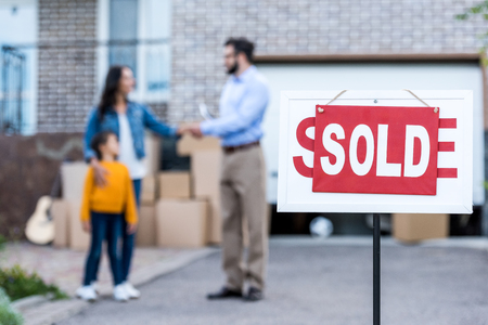 Photo for realtor making deal with single mother with sold signboard on foreground - Royalty Free Image
