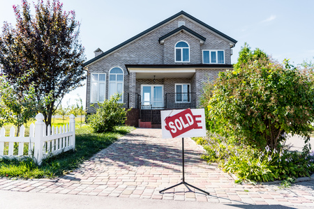 Photo pour beautiful house with sign sold standing on pathway - image libre de droit