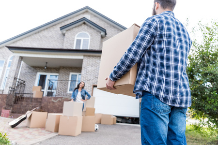 Photo pour young couple with boxes moving into new house - image libre de droit
