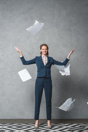 Foto de smiling businesswoman in suit looking at camera while throwing documents - Imagen libre de derechos