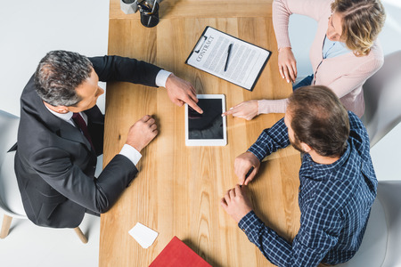 Photo pour overhead view of lawyer and clients using tablet together during meeting - image libre de droit