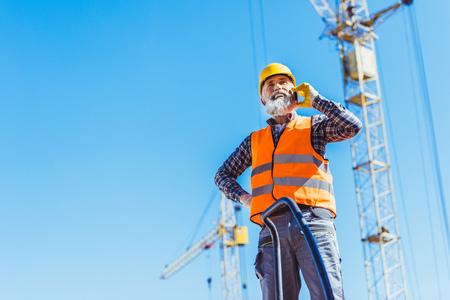 Foto de Smiling construction worker in reflective vest and hardhat talking on smartphone - Imagen libre de derechos