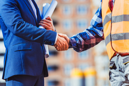 Foto de Cropped shot of construction worker in reflective vest shaking hands with businessman - Imagen libre de derechos
