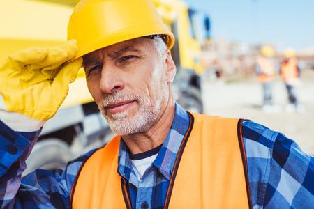 Foto de Portrait shot of worker in reflective vest adjusting his hardhat and looking at camera - Imagen libre de derechos