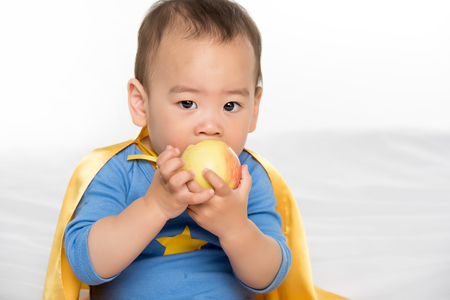 Photo pour portrait of cute asian toddler in superhero cape eating fresh apple isolated on white - image libre de droit