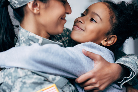 Foto de happy african american daughter hugging mother in military uniform at home - Imagen libre de derechos