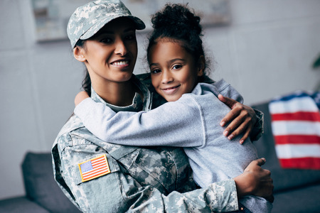 Foto de smiling african american daughter hugging mother in military uniform at home - Imagen libre de derechos
