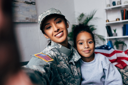 Foto de smiling african american daughter and soldier in military uniform taking selfie at home - Imagen libre de derechos