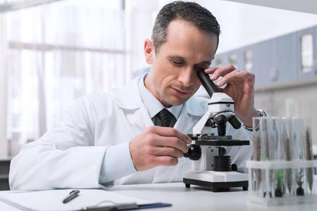 Foto de Focused male scientist in white coat doing a microscope sample analysis in chemical lab - Imagen libre de derechos