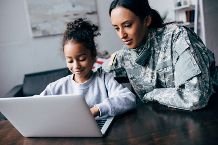 Photo pour african american mother in military uniform and daughter using laptop at home - image libre de droit