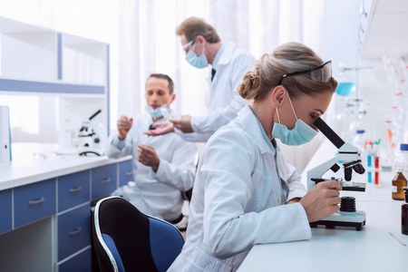 Photo for Medical worker in lab coat and sterile mask, doing a microscope analysis while her colleague are working behind - Royalty Free Image