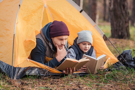 Photo for father and son reading books while lying together in tent - Royalty Free Image