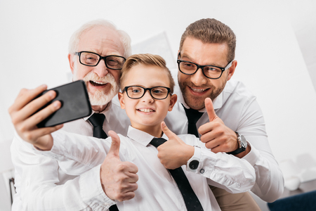 Foto de Father, son and grandfather wearing formal clothing and glasses taking a selfie with smartphone - Imagen libre de derechos