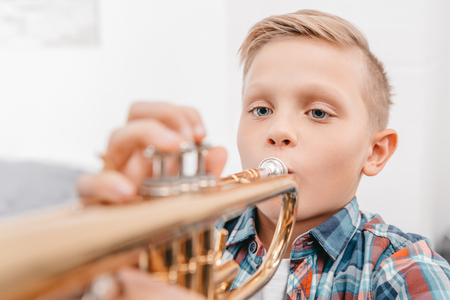 Photo for Portrait shot of young boy practicing playing trumpet - Royalty Free Image