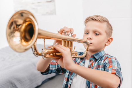 Photo for Young boy practicing playing trumpet in living room at home - Royalty Free Image