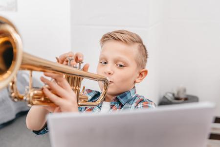 Foto de Young boy practicing playing trumpet in living room at home - Imagen libre de derechos