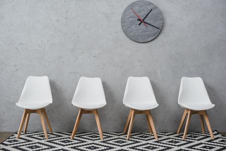 Foto de Row of empty white chairs in a waiting room at company with wall clock - Imagen libre de derechos