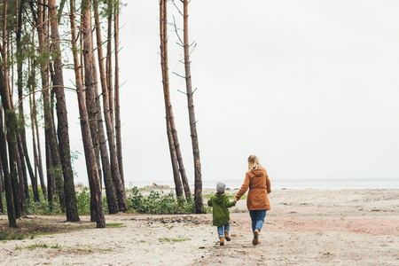 Photo for mother and son walking together on nature by sandy coast - Royalty Free Image