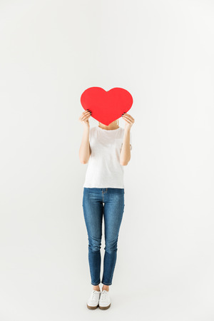 Photo for young woman hiding face behind red heart symbol isolated on white - Royalty Free Image